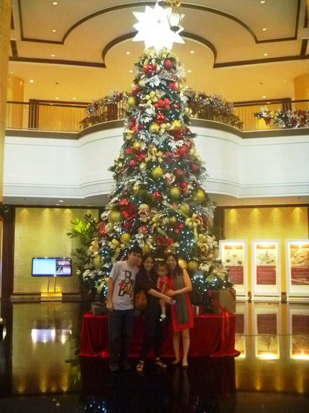 Posing in front of the lobby's huge Christmas tree prior to leaving