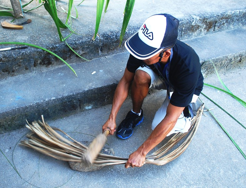 Beating dried bariw leaves with a wooden club (pagpalpag)