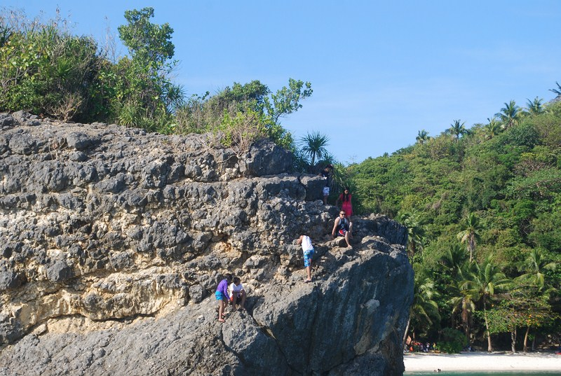Visitors making their way to the beach via the power plant and limestone formations