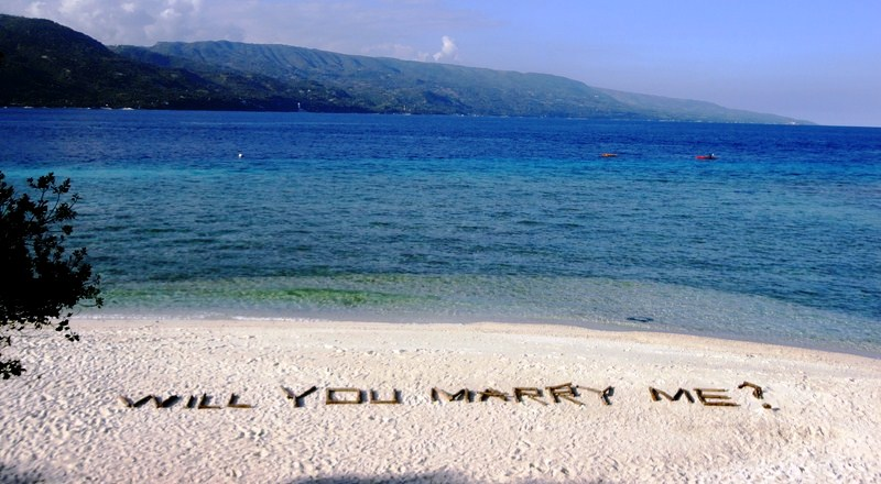 A marriage proposal etched on the sand