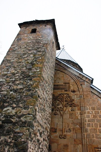 The tall, narrow watchtower adjacent to the west wall of the church
