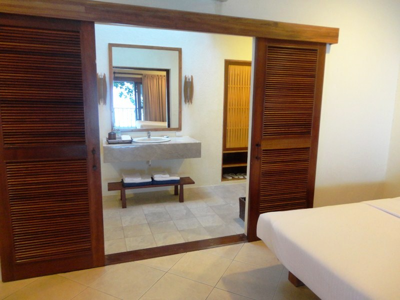 Wooden sliding louver doors leading to the bathroom