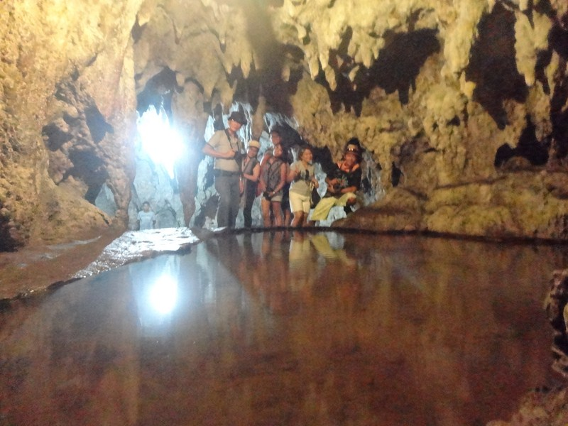 Media team posing beside a cave pool