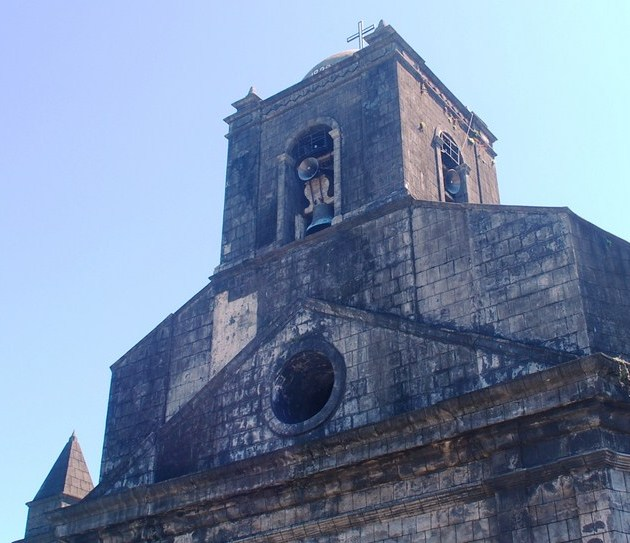 The centrally located, square bell tower and triangular pediment
