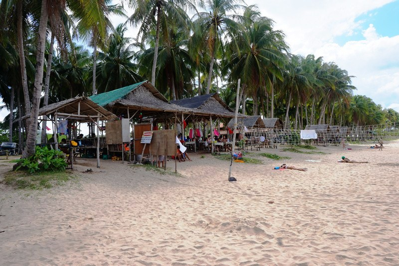 Eateries and picnic sheds along the palm-fringed beach